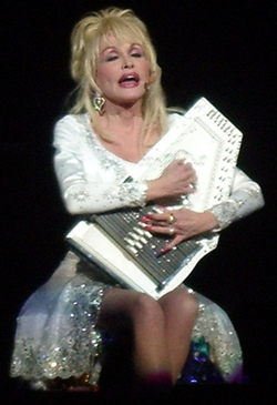 Dolly Parton playing a white bedazzled autoharp!